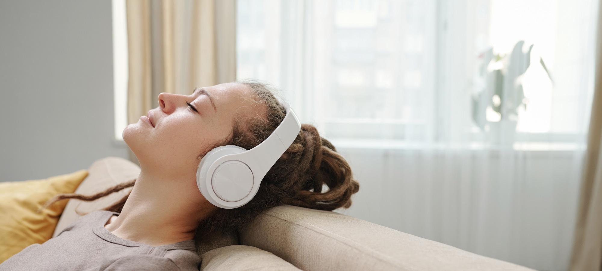 Chica en sofa escuchando musica